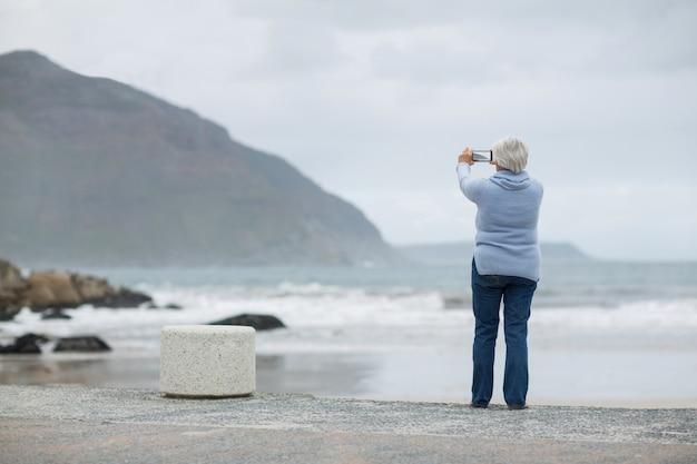 Donna senior che fotografa paesaggio facendo uso del telefono cellulare sulla spiaggia