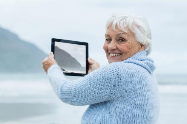 Donna senior che fotografa paesaggio facendo uso della compressa digitale