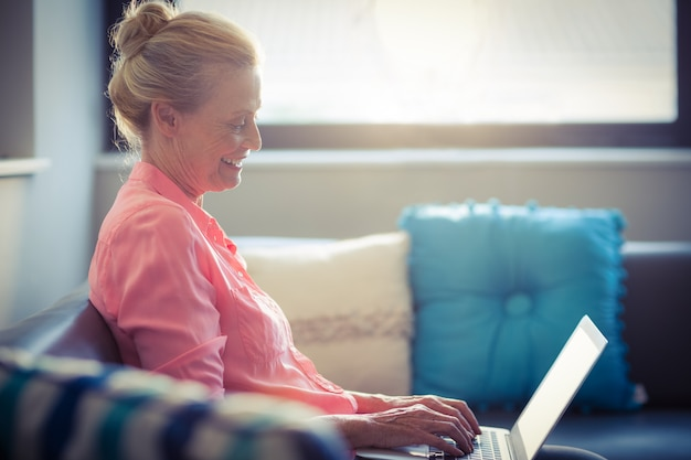 Donna senior che per mezzo del computer portatile