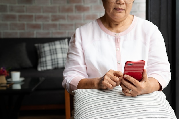 Donna senior che per mezzo della seduta bianca del telefono cellulare sul sofà a casa