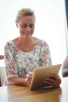 Donna senior che per mezzo di una compressa digitale