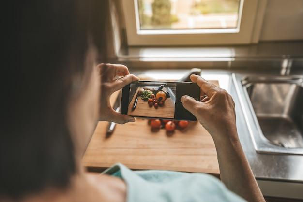 Donna senior che prende una fotografia con lo smartphone che cucina le verdure a casa