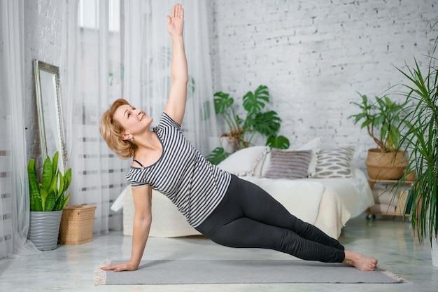 Donna senior che si esercita a casa, il concetto di uno stile di vita sano, forma fisica e yoga