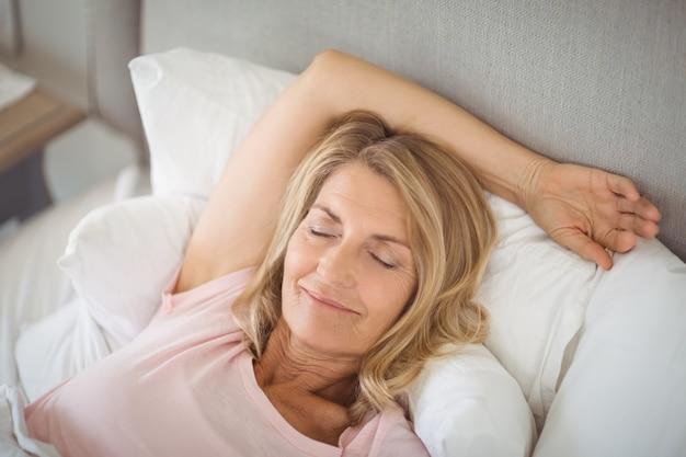 Donna senior che si rilassa a letto