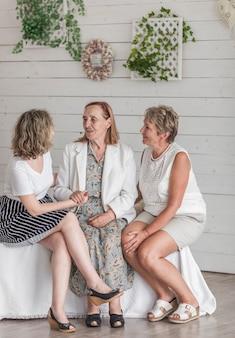 Donna senior che si siede sul sofà con sua figlia e nipote a casa