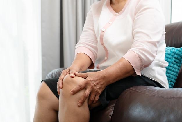 Donna senior che soffre dal dolore al ginocchio a casa, concetto di problema sanitario