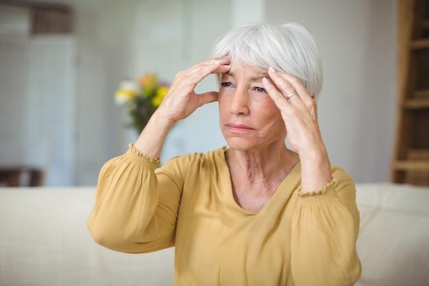 Donna senior che soffre di mal di testa in salotto