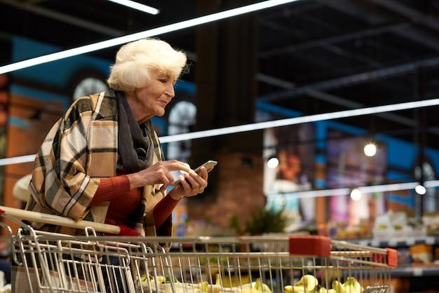 Donna senior che utilizza smartphone nel supermercato