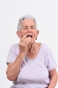 Donna senior con dolore sul labbro su fondo bianco