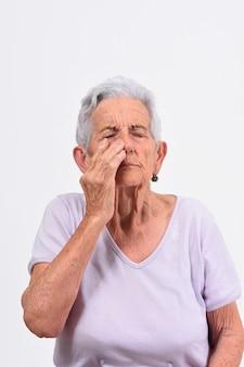 Donna senior con dolore sul naso su fondo bianco