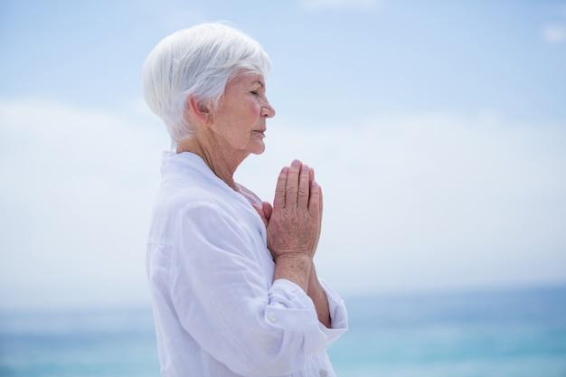 Donna senior con le mani giunte alla spiaggia contro il cielo
