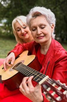 Donna senior del primo piano che gioca chitarra