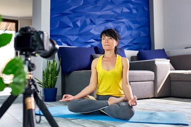 Donna senior di blogger con forma esile del corpo in abiti sportivi che fanno yoga a casa.