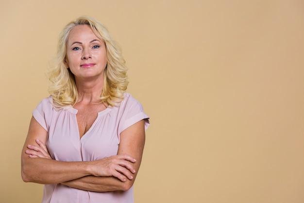 Donna senior di smiley che esamina la macchina fotografica con priorità bassa beige