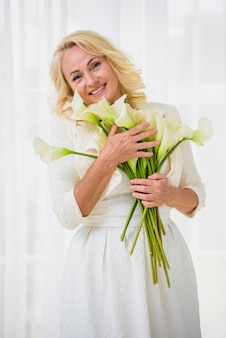 Donna senior di smiley che tiene un mazzo di fiori