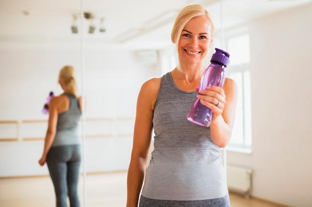 Donna senior di smiley che tiene una bottiglia di acqua