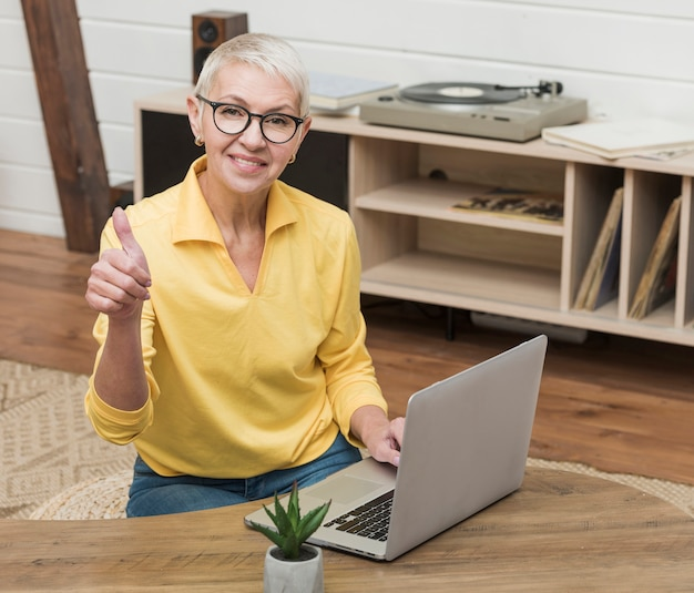 Donna senior di smiley dell'angolo alto che per mezzo di un computer portatile