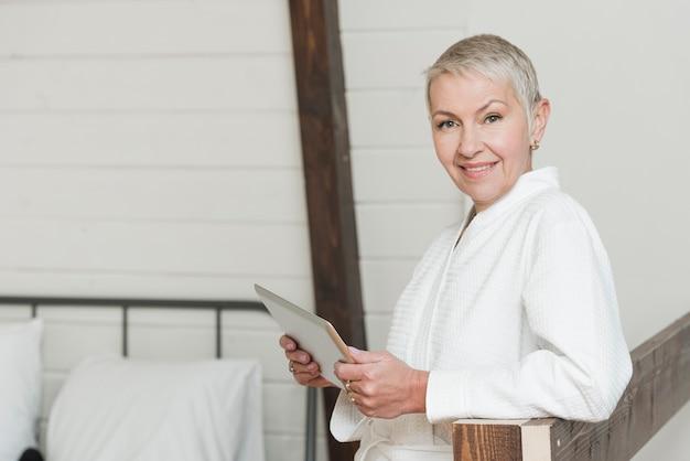 Donna senior di vista laterale che vive uno stile di vita moderno