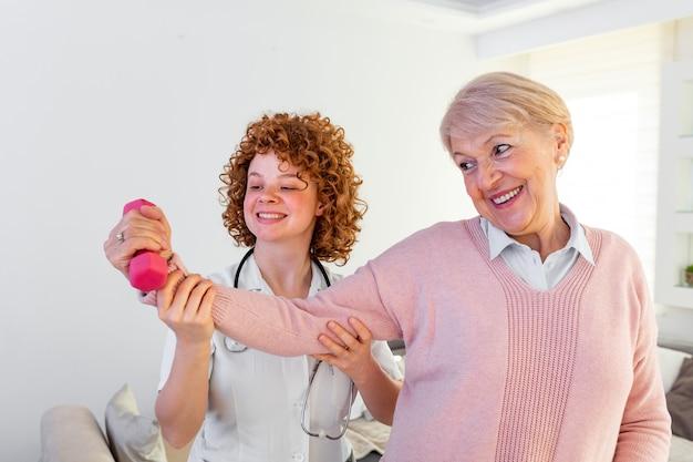 Donna senior dopo il colpo a casa di cura che si esercita con il fisioterapista professionista.