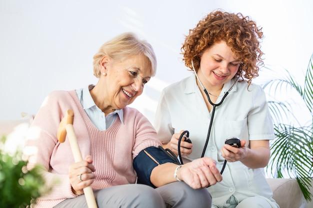 Donna senior felice che fa misurare la sua pressione sanguigna in una casa di cura dal suo badante.