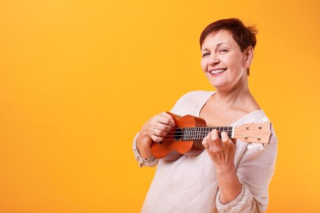 Donna senior felice che gioca ukulele