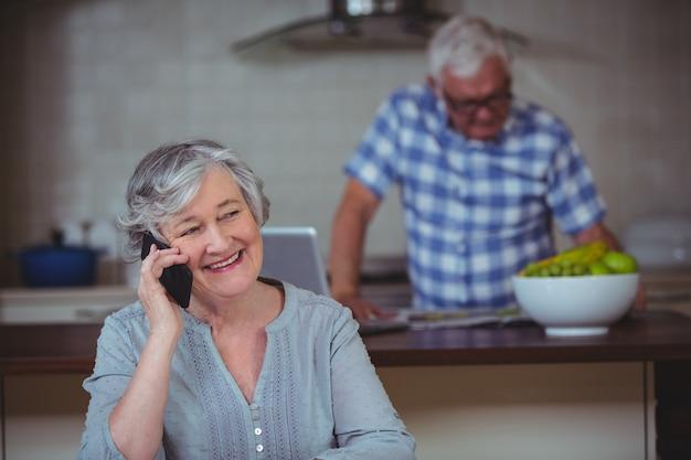 Donna senior felice che parla sul telefono in cucina