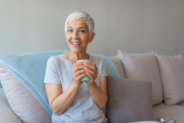 Donna senior felice che si siede su uno strato mentre sta bevendo una tazza di caffè.