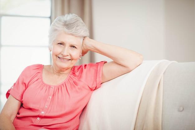 Donna senior felice che si siede sul sofà in salone