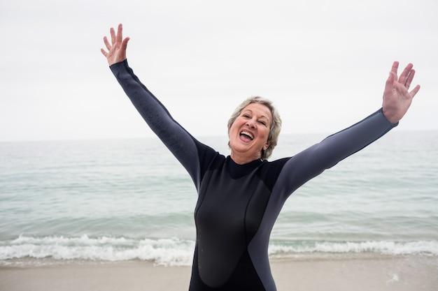 Donna senior felice che sta sulla spiaggia