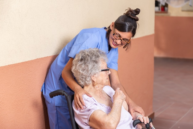 Donna senior felice con il bastone da passeggio in sedia a rotelle con il suo badante a casa