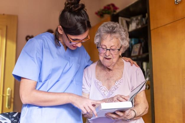 Donna senior felice con il suo badante a casa che legge un libro