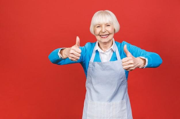 Donna senior nella condizione del grembiule isolata su fondo rosso. è una brava casalinga. le piace cucinare cibi gustosi. pollice in alto segno.