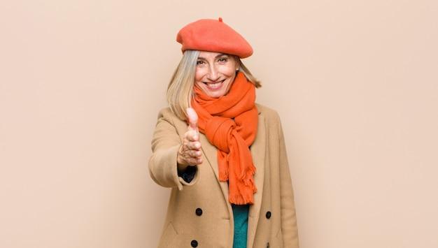 Donna senior o di mezza età che sorride, sembra felice, fiduciosa e amichevole, che offre una stretta di mano per chiudere un affare, collaborando