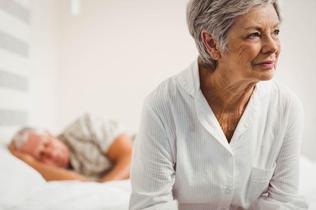Donna senior preoccupata che si siede sul letto in camera da letto