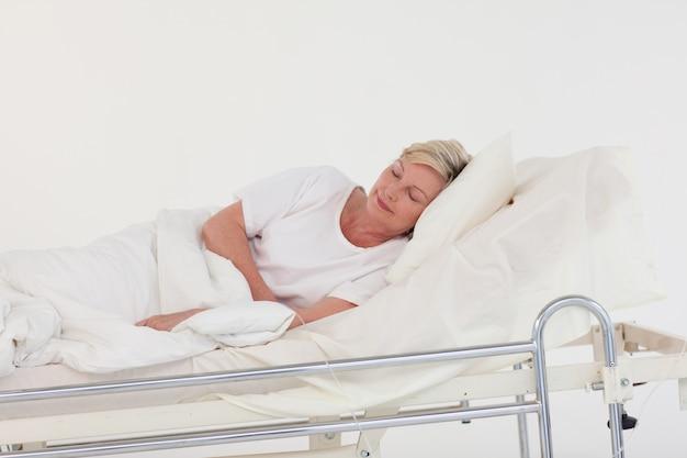 Donna senior rilassata che si trova su un letto