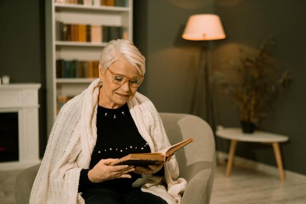 Donna senior saggia in occhiali che legge vecchio libro