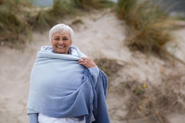 Donna senior sorridente avvolta in scialle alla spiaggia