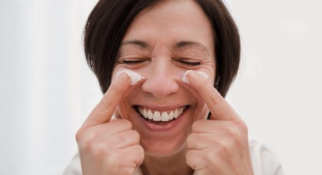 Donna senior sorridente che applica la crema di fronte antinvecchiamento a casa. donna matura felice che usando idratante di giorno