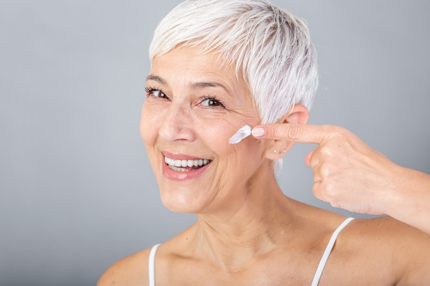 Donna senior sorridente che applica lozione anti-invecchiamento per rimuovere le occhiaie sotto gli occhi. donna matura che usando crema cosmetica per nascondere le rughe. lady utilizza un idratante da giorno per contrastare l'invecchiamento della pelle.