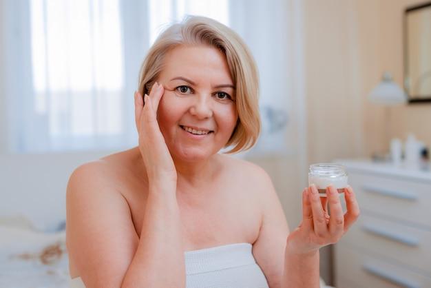 Donna senior sorridente che applica lozione anti-invecchiamento per rimuovere le occhiaie sotto gli occhi.