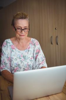 Donna senior sorridente che per mezzo di un computer portatile
