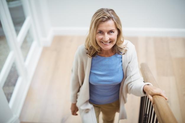 Donna senior sorridente che scala di sopra a casa