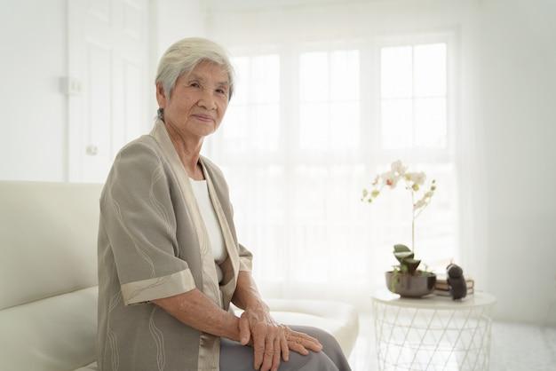 Donna senior sorridente che si siede sul sofà e che esamina macchina fotografica. risveglia la vecchia con i capelli grigi e il pigiama nella luce del primo mattino. ritratto della donna anziana che si trova e che sorride.
