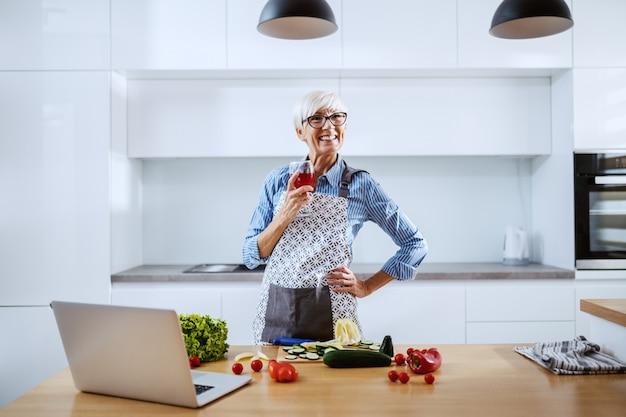 Donna senior sorridente in grembiule che sta nella cucina, bevendo vino e preparando cena sana