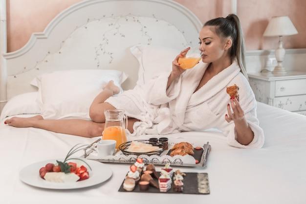 Donna sensuale che beve il succo sul letto