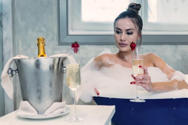 Donna sensuale con champagne che prende bagno a casa