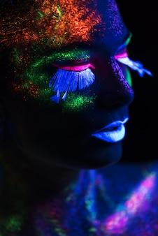 Donna sensuale nel trucco di vernice fluorescente. avvicinamento