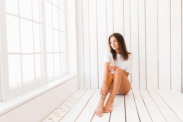 Donna sensuale rilassante vicino alla finestra