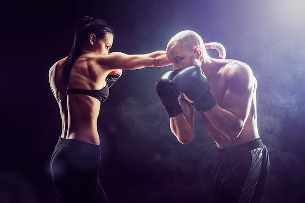 Donna senza camicia che si esercita con l'istruttore alla lezione di boxe e di autodifesa lotta femminile e maschio