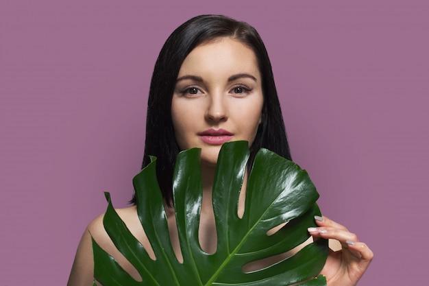 Donna senza trucco con foglia verde e bellezza naturale